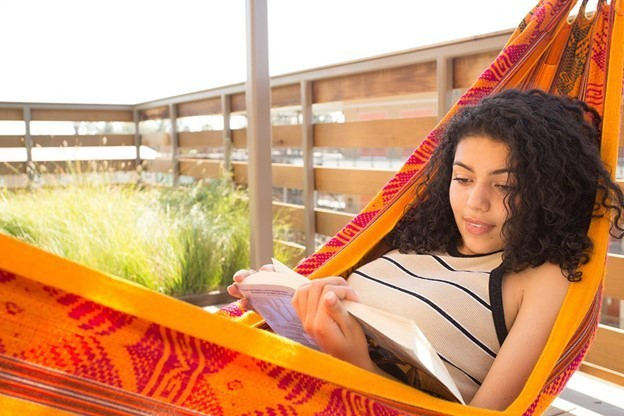 Student reading a book in a hammock on campus