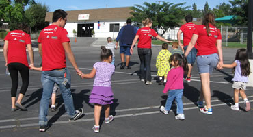 Jumpstart students lead young children on a playground.