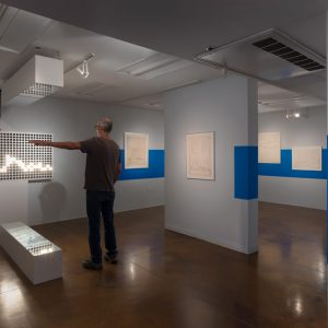 A man interacts with a kinetic sculpture in the Lenzner Family Art Gallery at Pitzer College.