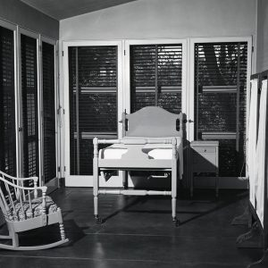 Archive photo of one of the sun rooms in the infirmary with a bed, a chair and a privacy curtain.