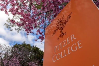 Pitzer College orange sign with pink ornamental plum blossoms.