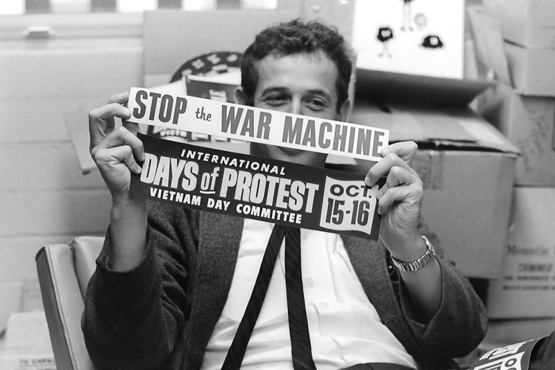 """Edward Sampson, Associate Professor of Social Psychology, holds two bumper stickers: """"International Days of Protest Vietnam Day Committee, Oct. 15–16"""" and """"Stop the War Machine."""" Taken September 16, 1965 in his office."""