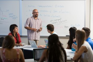 Adrian Pantoja, professor of Political Studies and Chicano studies, teaching in the classroom with a whiteboard in the background.