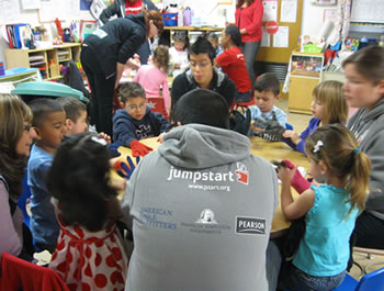 Jumpstart students work in a classroom of young children.