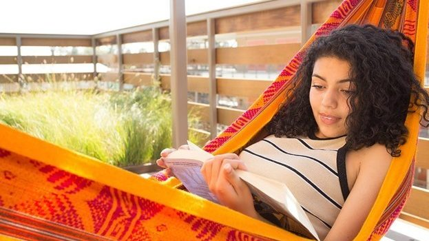 Student reading a book on campus
