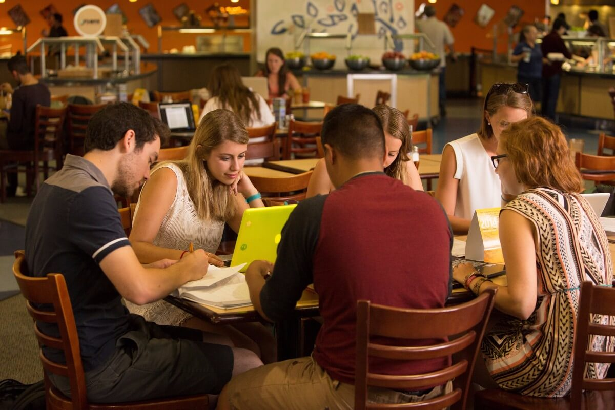 Students studying at a table in the dining hall in the afternoon