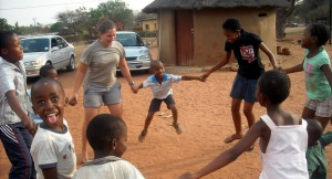 Children in Botswana and Pitzer student hold hands in a circle.