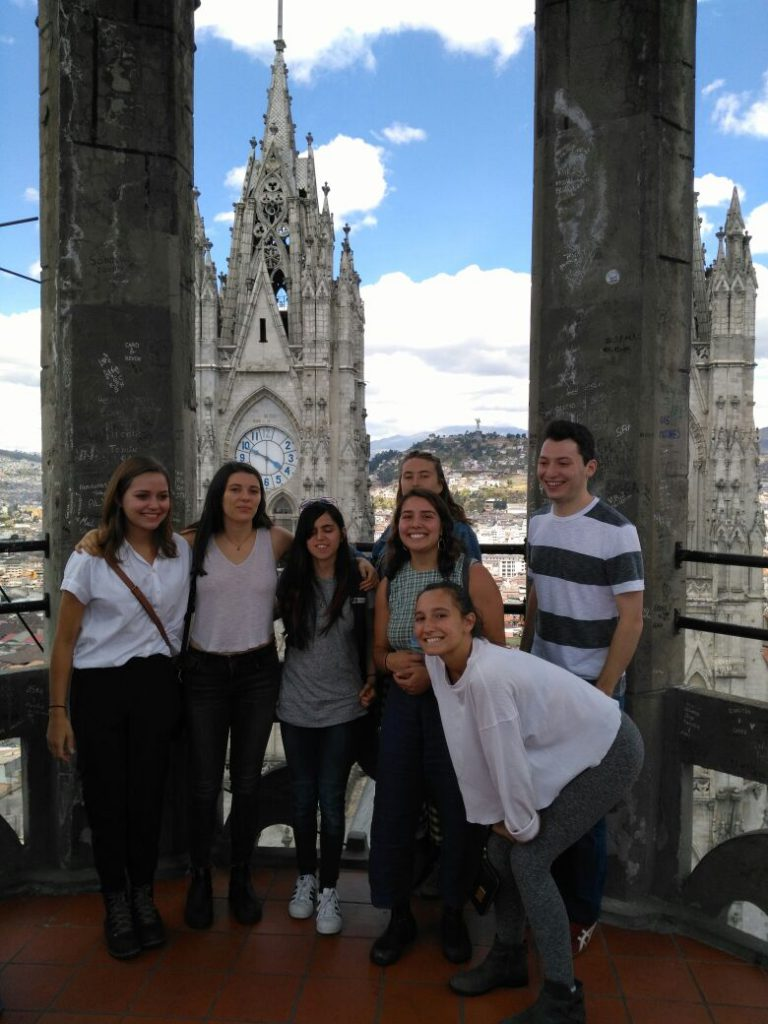 Photo of students with a cathedral in the background.